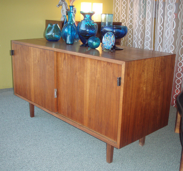 Vintage Florence Knoll Petite Credenza, in walnut with slider doors and open storage inside. Retains original black leather pulls. 