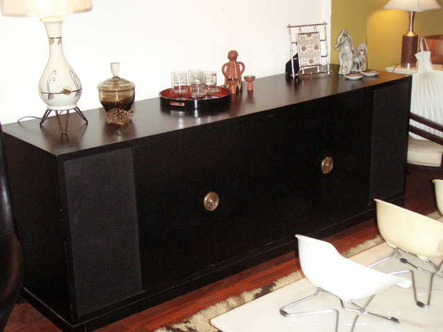 Magnificent black lacquered two door console in the style of Tommi Parzinger  c.1950 with beautiful bronze patinated hardware. Two doors reveal open space storage(TV or audio) on the left and divided section for records on the right.  Two additional side bar sections covered for speakers or can be customized for additional display/storage.   SOLD