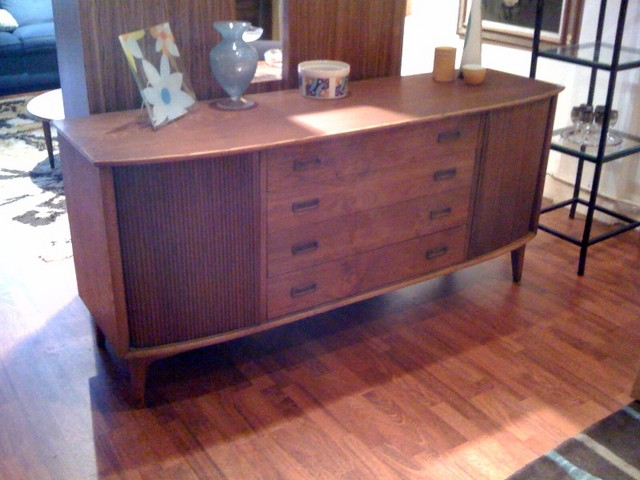 Bow-fronted teak credenza.  Beautiful wood drawer handles on each of the four drawers--the top drawer has silverware separations-- and great tambour door details enclosing cabinets each with adjustable shelves.  Teak is in very good condition.  68 inches wide, 20.5 inches deep, 31.5 inches tall.  SALE $700  SKU# F0057