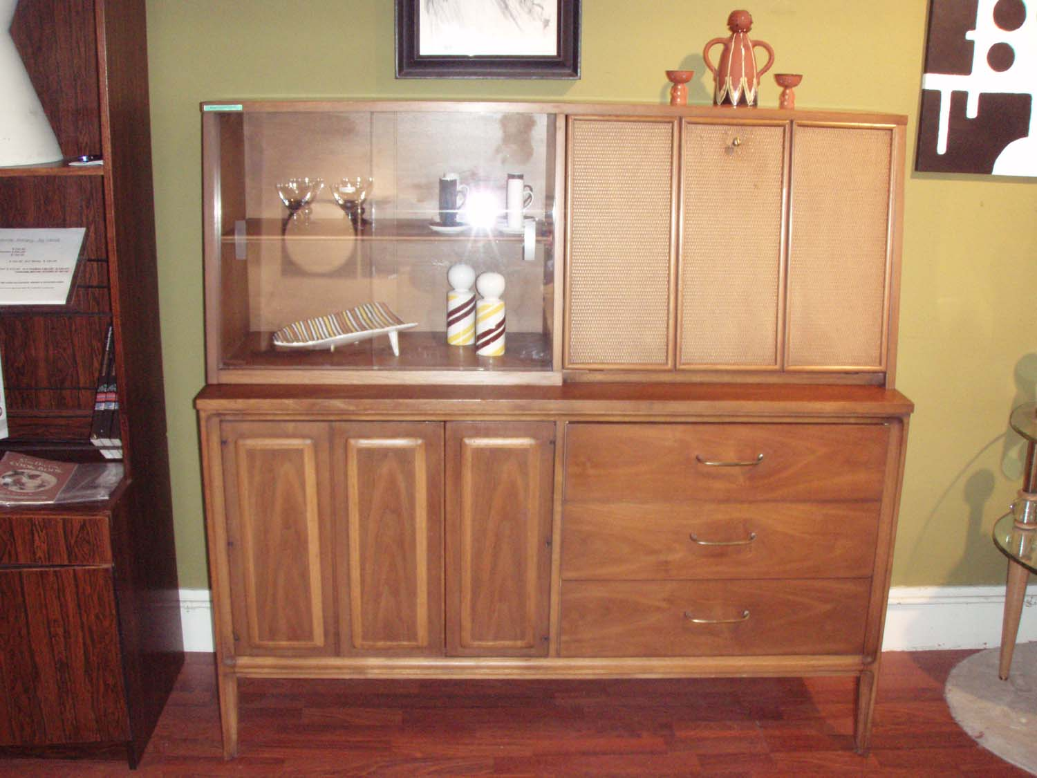 """Danish modern walnut credenza and china cabinet/bar hutch. This piece is not to large or tall, and the hutch is removable. There is open storage on left behind double door(panels) and then 3 generous drawers on the right. The top hutch has (2) glass sliders for display and a cool drop down bar w/ caning detail! 54""""L x 18""""D x54 1/2""""H  (31""""H without hutch) $1195.00  (SALE $999.00)  Shipping to NY or Florida $395.00 including insurance and white glove delivery!"""