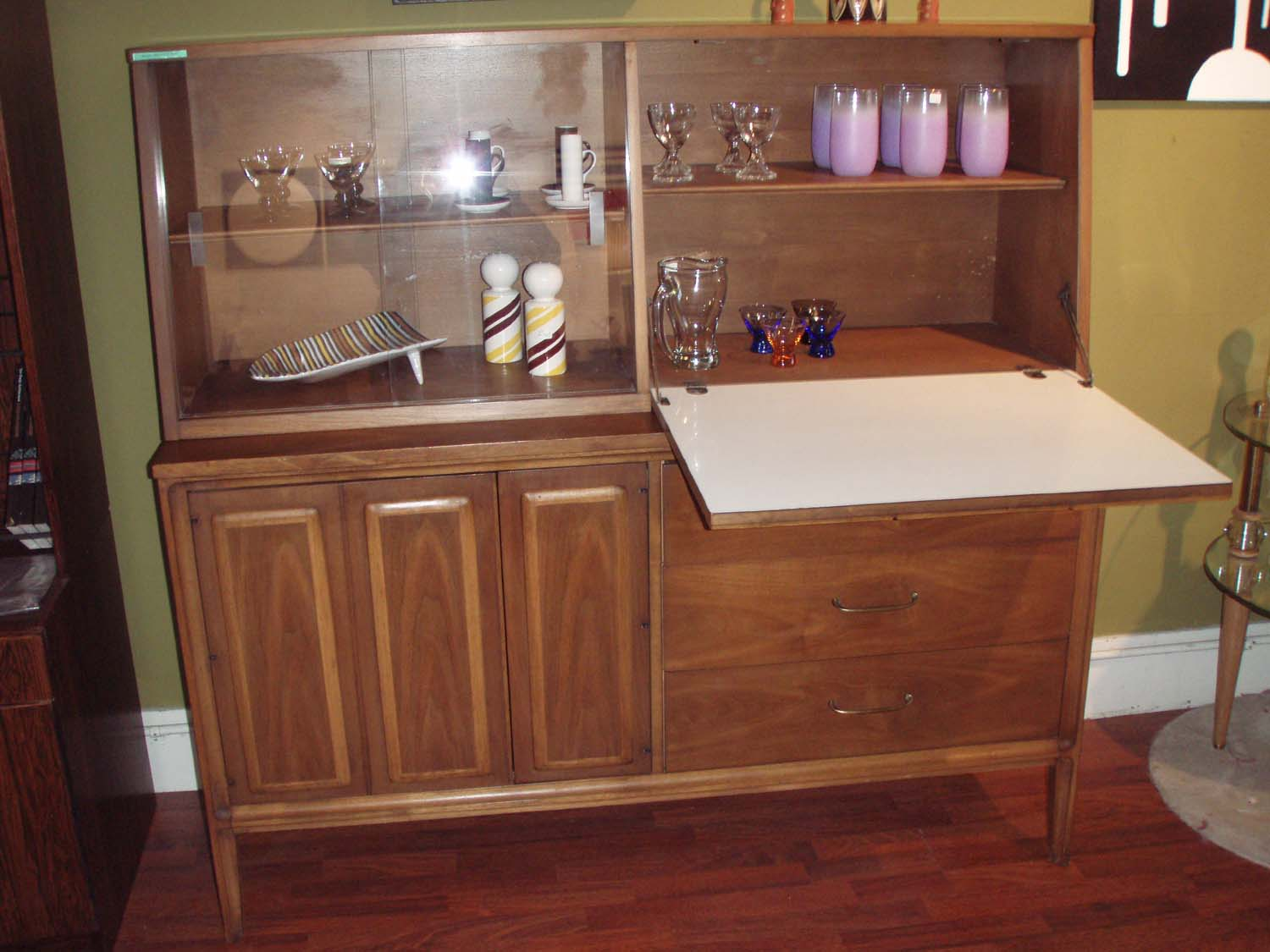 Danish modern walnut credenza and china cabinet/bar hutch. This piece is not to large or tall, and the hutch is removable. There is open storage on left behind double door(panels) and then 3 generous drawers on the right. THe top hutch has (2) glass sliders for display and a cool drop down bar w/ caning detail! $1195.00