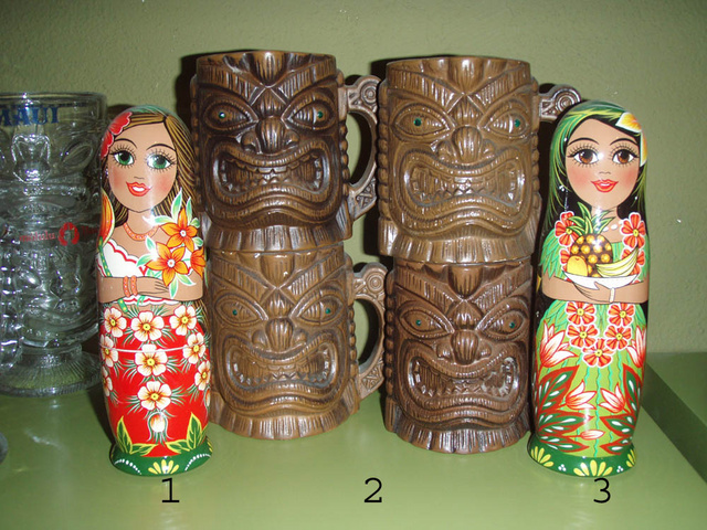 """These HULA DOLLS were created in  ST. PETERSBURG, RUSSIA by Matryoshka artists.  1. Hula Girl with Pineapple Bowl  7""""H, $25.00,   2. Tiki Mug w/handle(coffee mug style) and emerald green eyes (4 available) $30.00   3.Hula Girl with Birds of Paradise Fan  7""""H, $25.00,"""